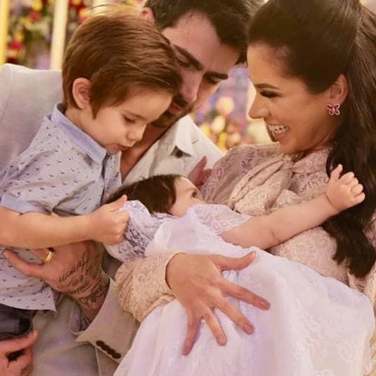 A pequena Linda sendo observado pela sua família durante seu batizado