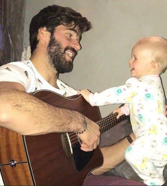 O papai Alisson tocando para a pequena Helena