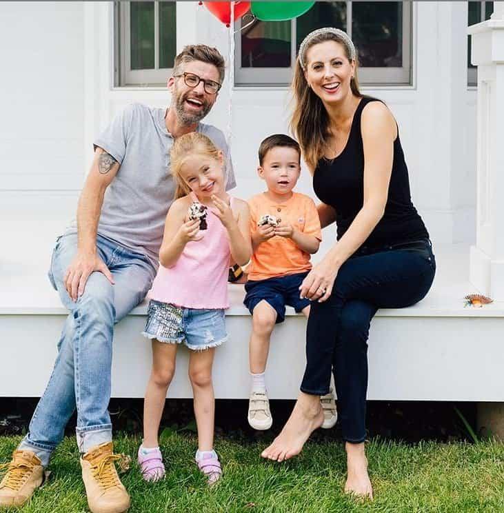 Atriz grávida ao lado do marido e dos dois filhos