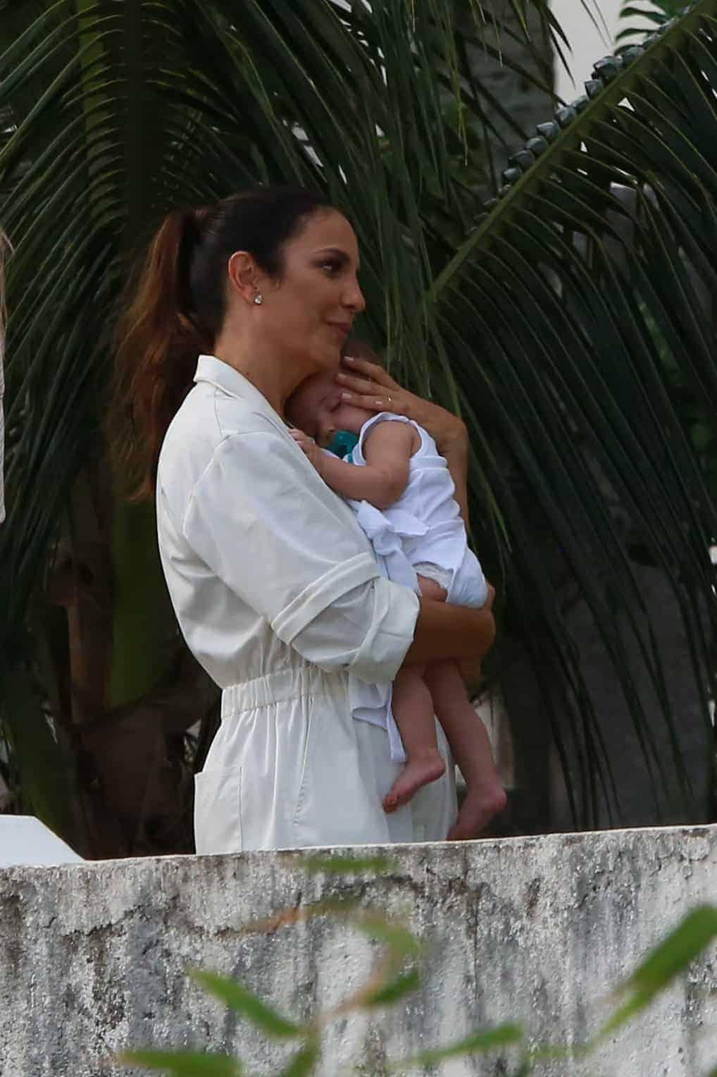 Uma das gêmeas no colo da cantora Ivete Sangalo antes do batizado