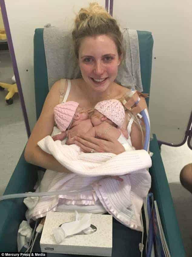 Amy segurando as duas filhas