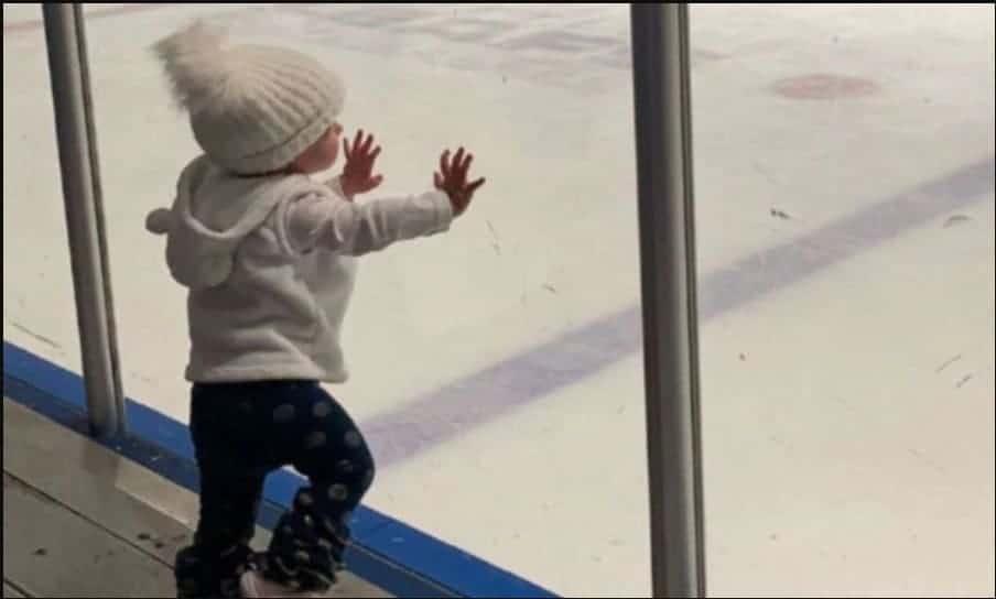 A bebê apoiando no vidro durante o jogo de hóquei do irmão
