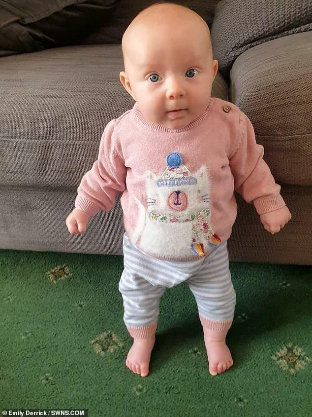 Bebê em pé sozinha com três meses