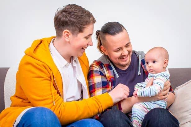 Homem trans ao lado de seu parceiro e com seu bebê no colo