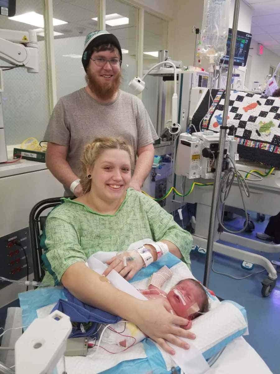 Pais com seu bebê pouco após ele nascer com doença rara