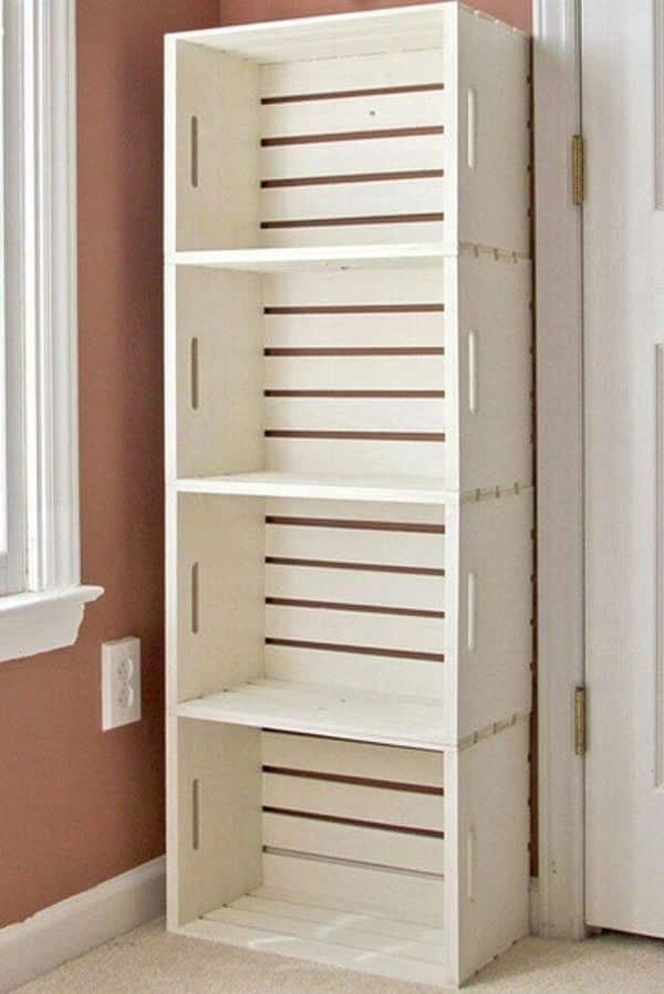 Caixotes brancos de feira empilhados na parede como estante do quarto de bebê