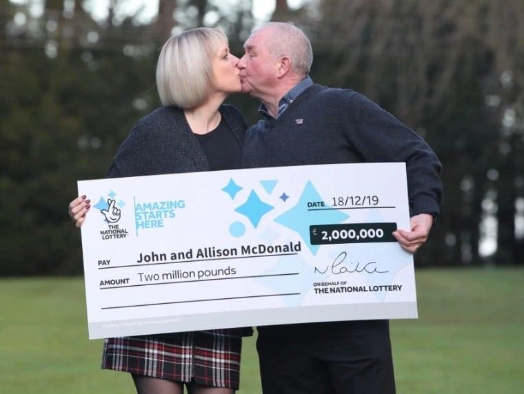 O casal com o prêmio que ganharam da loteria