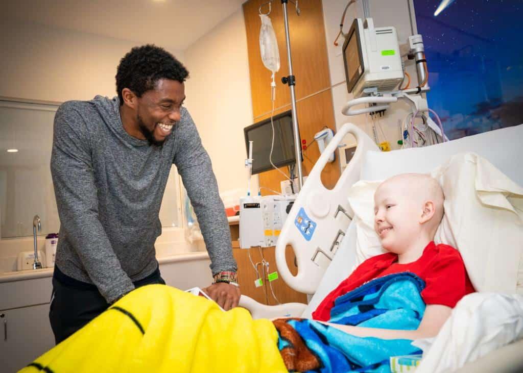 Chadwick Boseman visitando criança com câncer