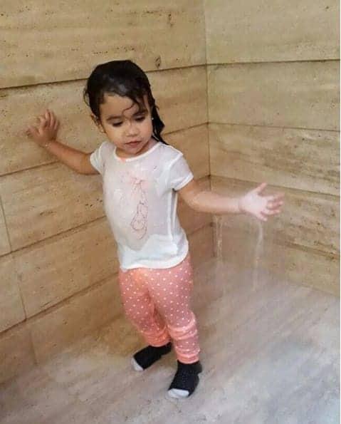 Maria Flor tomando banho vestida
