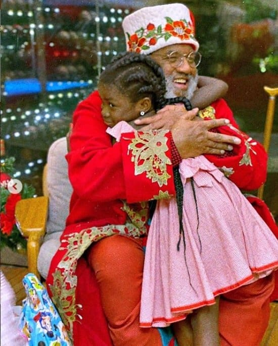 Titi dando um forte abraço no Papai Noel negro