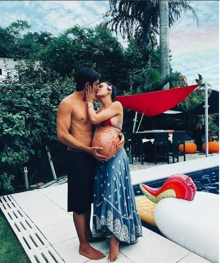 Isis Valverde com a barriga pintada ao lado do esposo