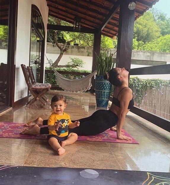 Isis Valverde praticando ioga ao lado do filho