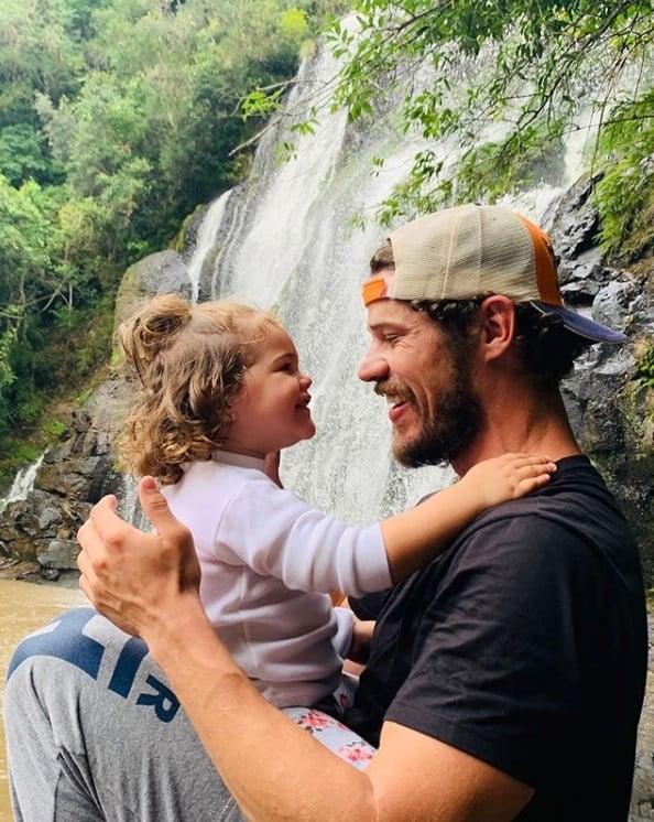 José Loreto com sua bebê diante da cachoeira