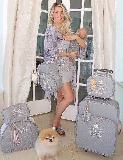 Karina Bacchi com seu filho no colo e rodeado de malas