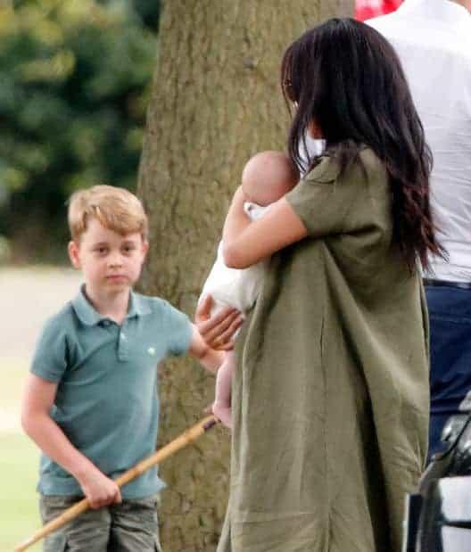 príncipe George, primogênito de Kate Middleton, olhando para Archie no colo de Meghan Markle