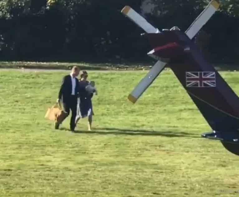 A duquesa Kale Middleton carregando o príncipe Louis no colo acompanhado do marido o príncipe William