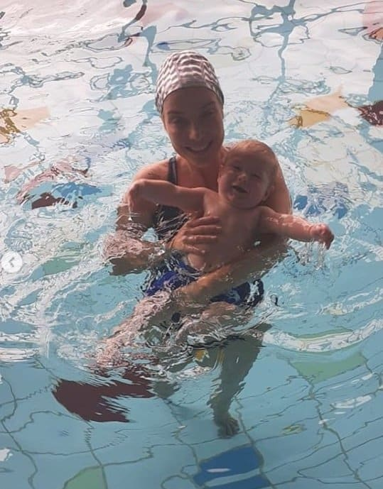 Cantora com seu bebê na aula de natação