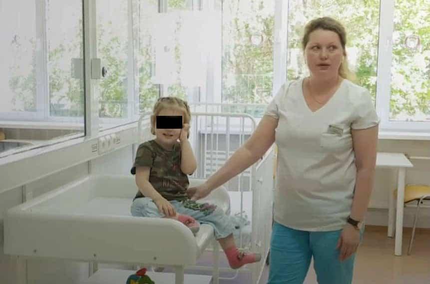 Ariana, menina que foi abandonada pela mãe, ao lado de uma enfermeira