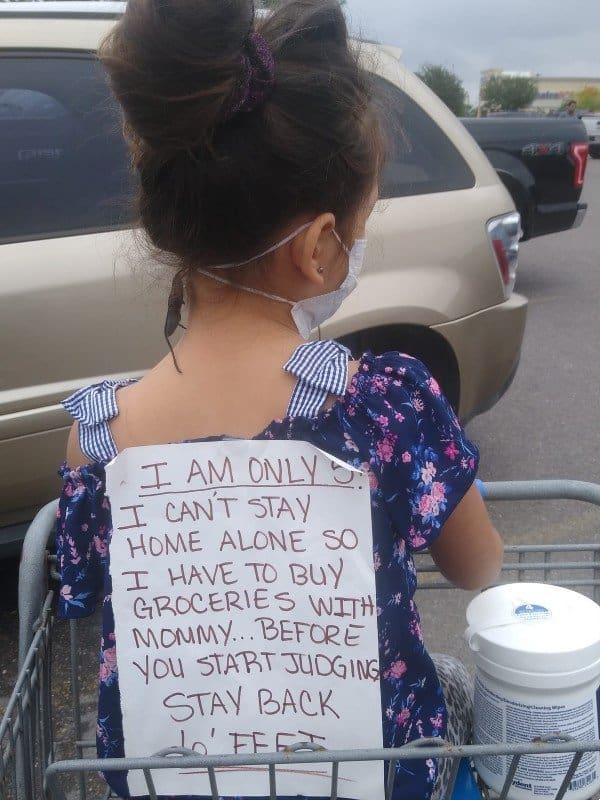 Menina com cartaz durante ida ao mercado
