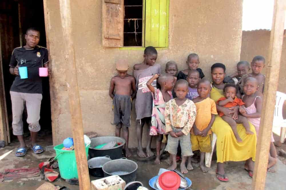 a mãe Mariam com alguns de seus filhos em frente a casa