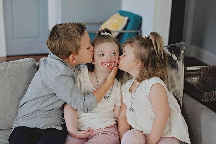 Sophia ganhando um beijo de seus irmãos