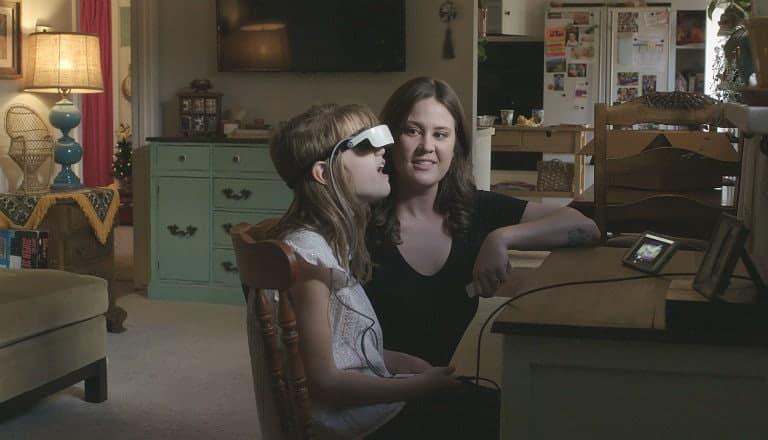 Menina usa óculos especiais para o computador