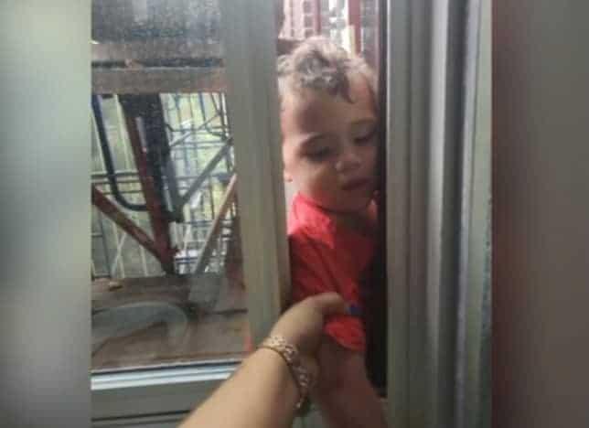 Menino de três anos sendo resgatado após arrancar ar condicionado