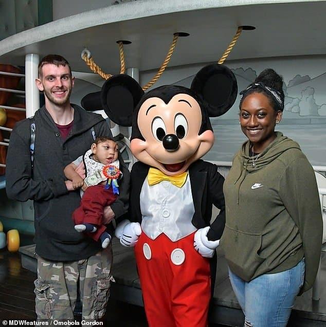 Menino e seus pais em encontrinho com o Mickey