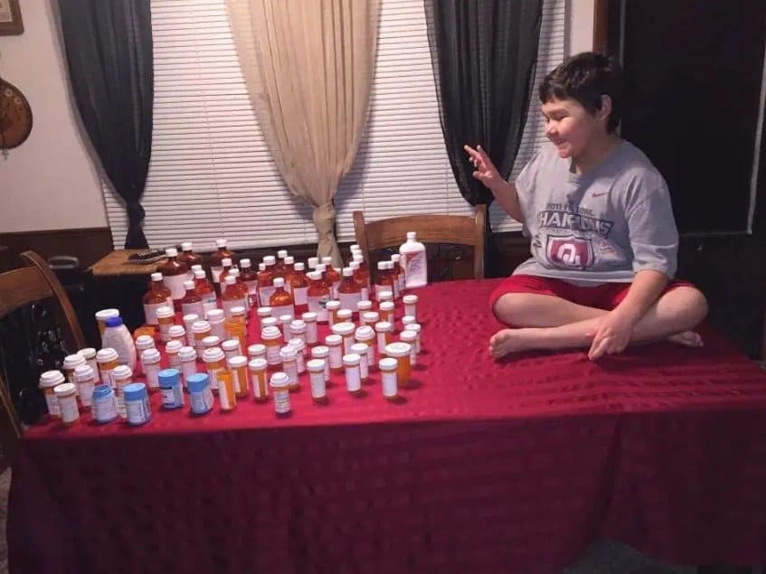 Menino com os frascos vazios dos remédios que tomou na quimioterapia