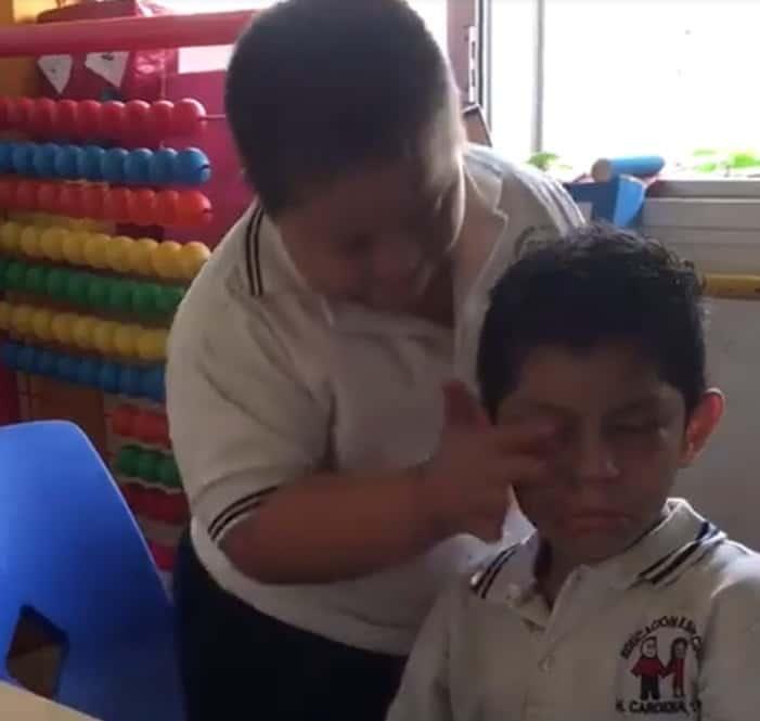 Menino com Síndrome de Down secando as lágrimas de seu colega