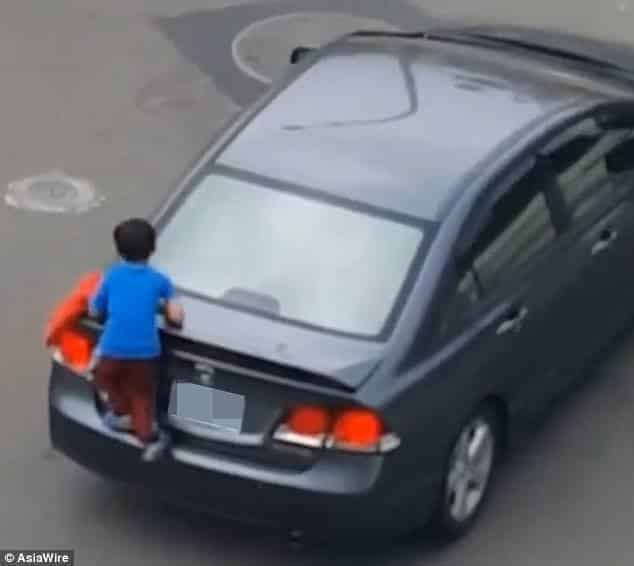 Nessa outra imagem o menino já está pendurado no carro de sua mãe