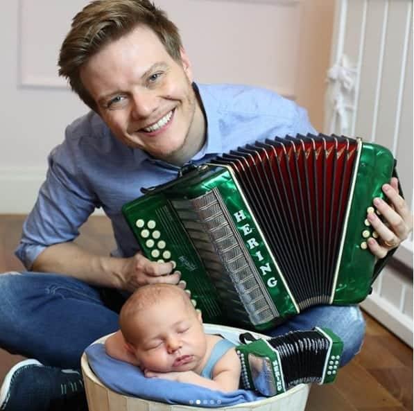 O cantor Michel Teló tocando para o bebê Teodoro