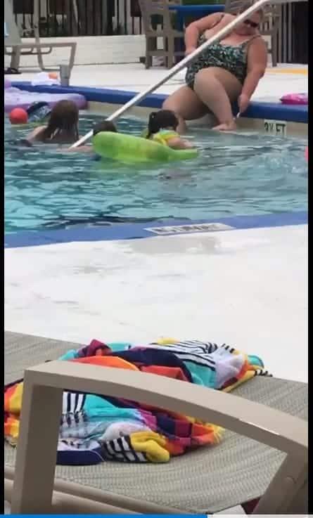 Numa piscina repleta de crianças uma mulher faz sua depilação