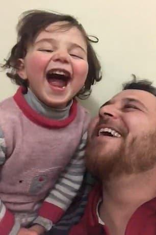 Pai tentando distrair sua filha pequena em bombardeio