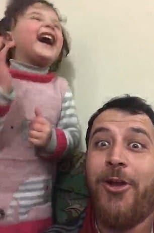 Pai brincando com a filha em meio a um bombardeio