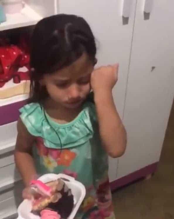 Menina emocionada ao ganhar pedaço de bolo no seu aniversário