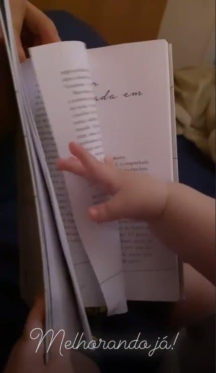Bebê de Paulo Gustavo com um livro em registro feito pelo pai Thales Bretas