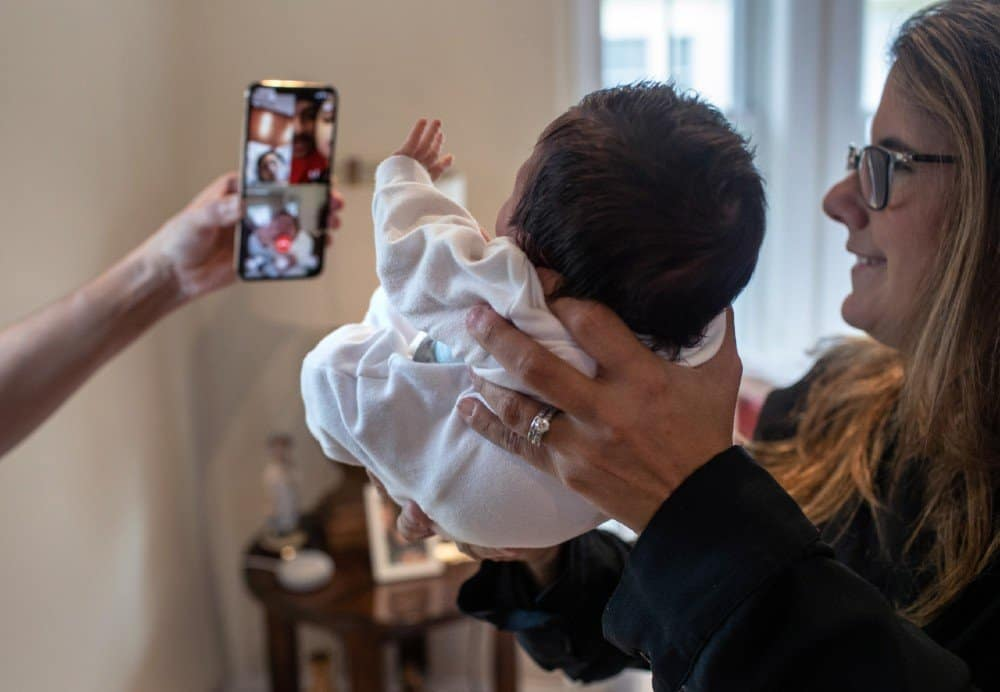 Professora fazendo chamada de vídeo do bebê com a família