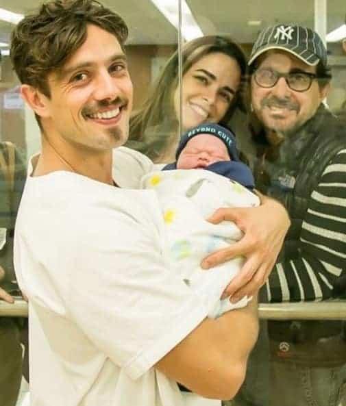 O ator Rafael Cardoso com o pequeno Valentim no colo e o vovô no fundo, o diretor Edson Spinello