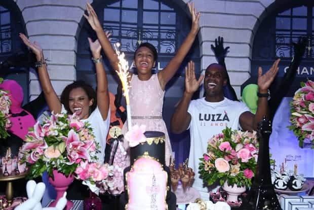 Luiza cantando parabéns junto com o seus pais