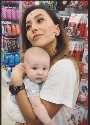 Sabrina Sato segurando um bebê no colo durante a compra do enxoval de sua bebê