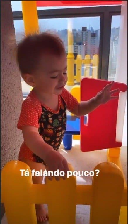 Zoe brincando em sua casinha de boneca
