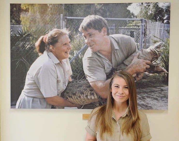 Bindi diante da foto do pai Steve Irwin e da avó