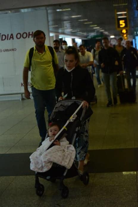 Thaeme de máscara no aeroporto com sua filha