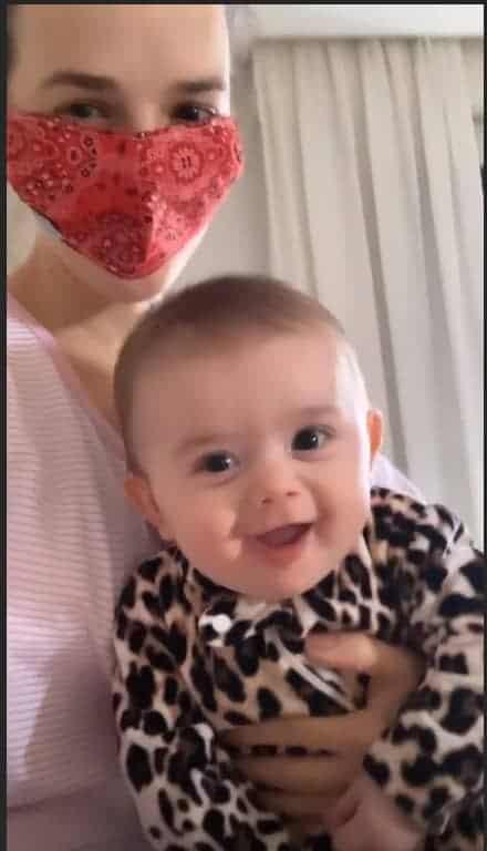 Thaeme com máscara ao lado da bebê Liz