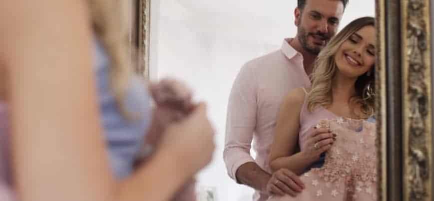 A cantora Thaeme Mariôto e o marido com o vestidinho da filha