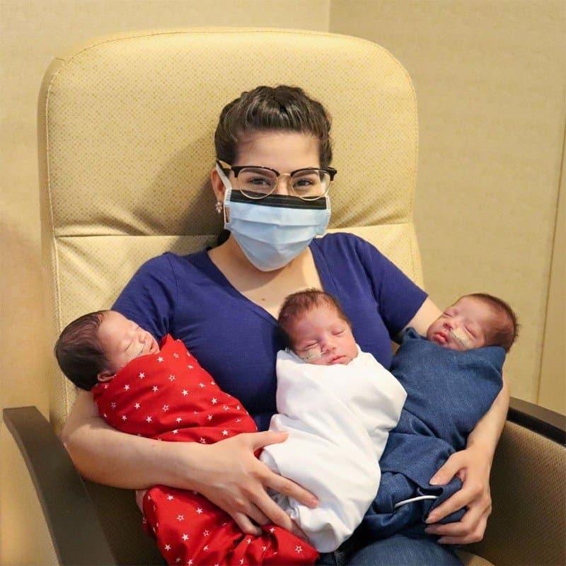 A mãe no hospital com seus bebês trigêmeos