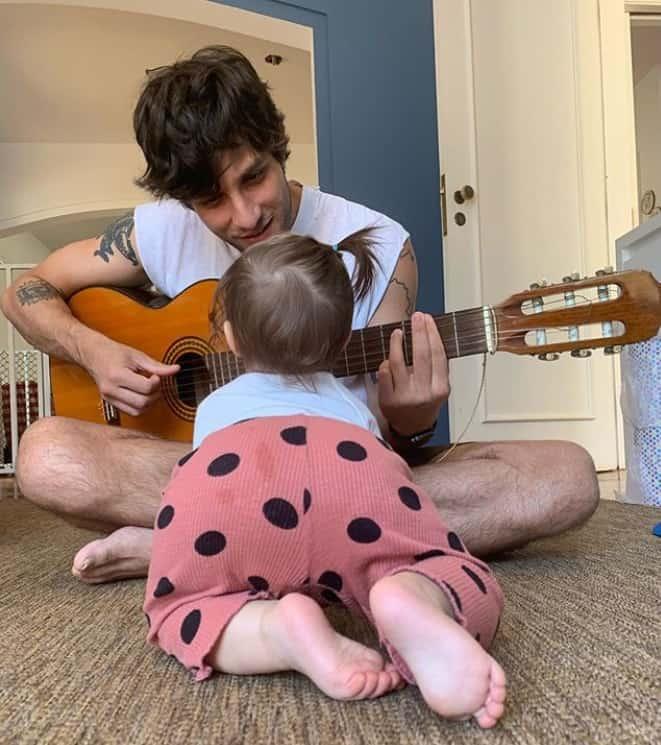 Chay Suede tocando violão para a filha em foto feita por Laura Neiva