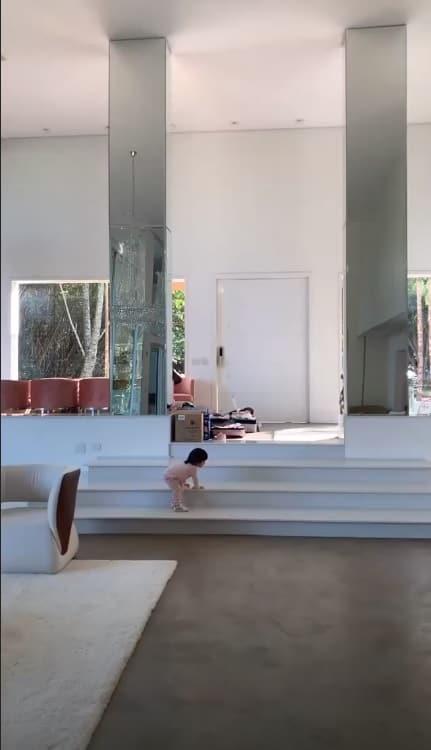 Filha de Mayra Cardi na sala da nova mansão da coach