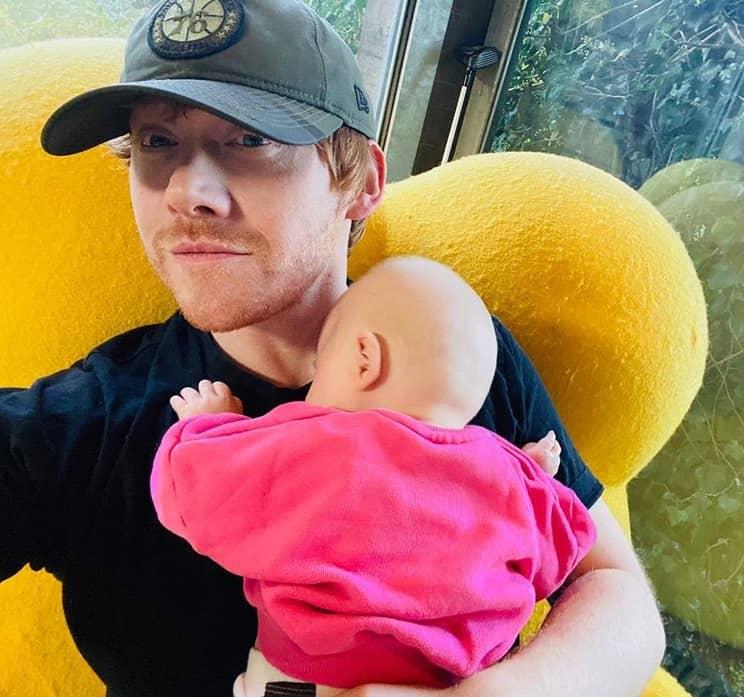Rupert Grint com sua bebê no colo